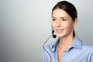 Attractive female call center operator, client services assistant or telemarketer wearing a headset looking at the camera with a charming friendly smile, on grey with copy space
