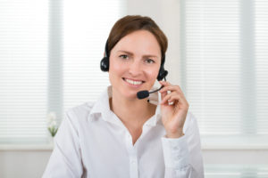 Portrait Of Young Female Operator With Headset In Call Center