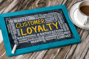 customer loyalty with related word cloud handwritten on blackboard