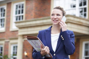 Female Realtor On Phone Outside Residential Property